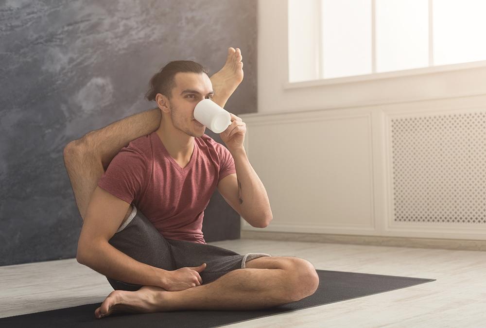 ヨガのポーズをしながらお茶を飲む男性