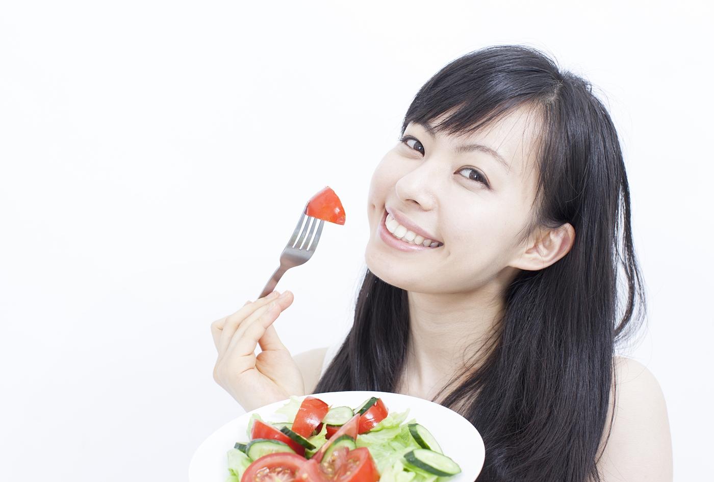笑顔でサラダを食べる女性