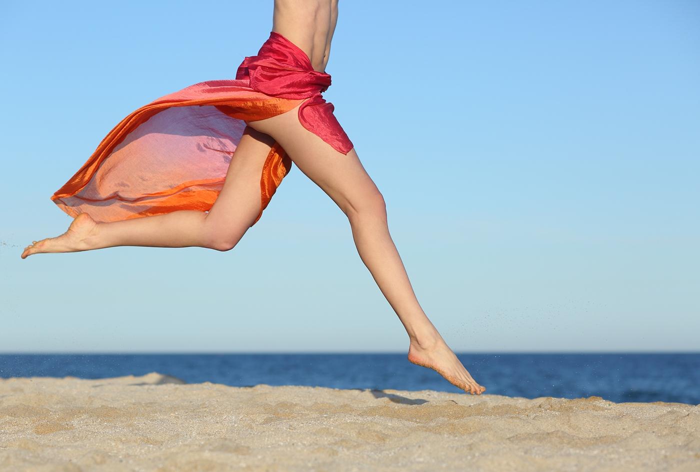 砂浜を走る女性の脚