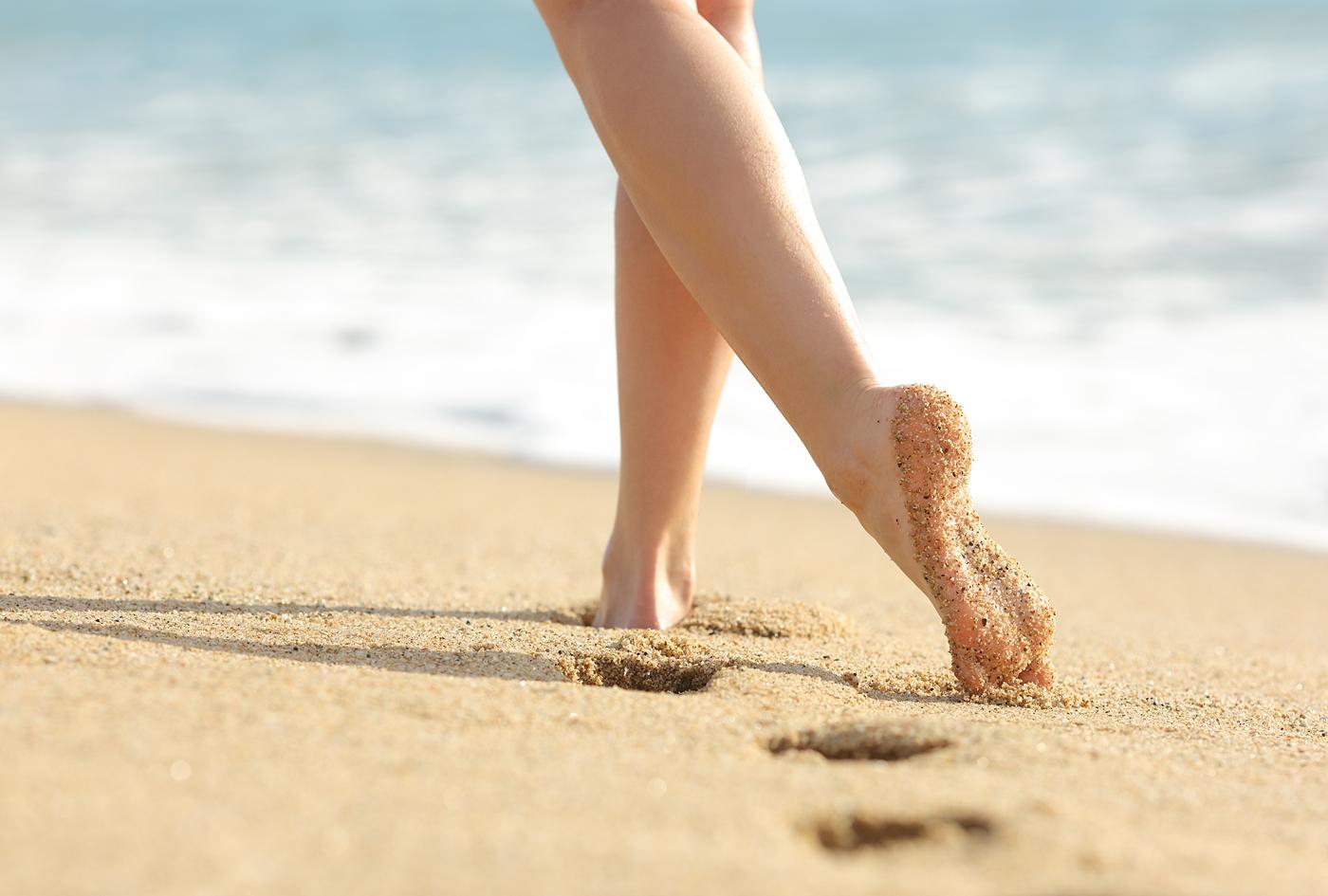 砂浜を歩く女性の脚