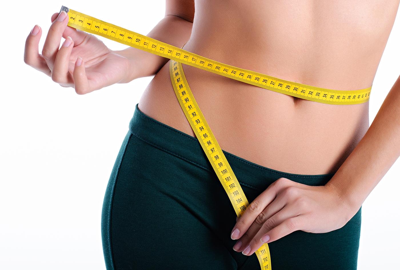 スパッツ姿でウエストサイズを測る女性