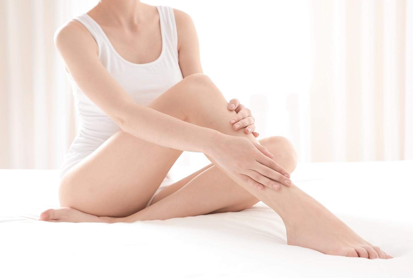 キャミソールで脚をケアする女性